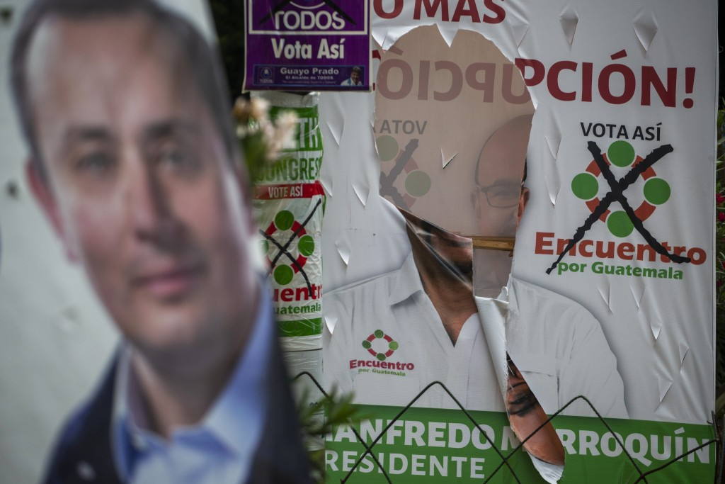 In this Thursday, June 13, 2019, photo, a vandalized campaign poster of Manfredo Marroquin, presidential candidate of the Encuentro political party, i