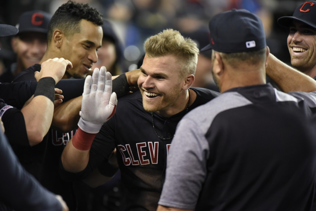Cleveland Indians' Jake Bauers, center, is congratulated by teammates after hitting a two-run home run against the Detroit Tigers in the top of the ei