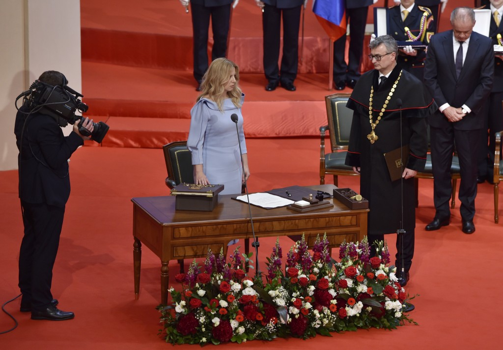 New Slovak President Zuzana Caputova takes her presidential oath as outgoing President Andrej Kiska, in the background at right, listens during a parl...