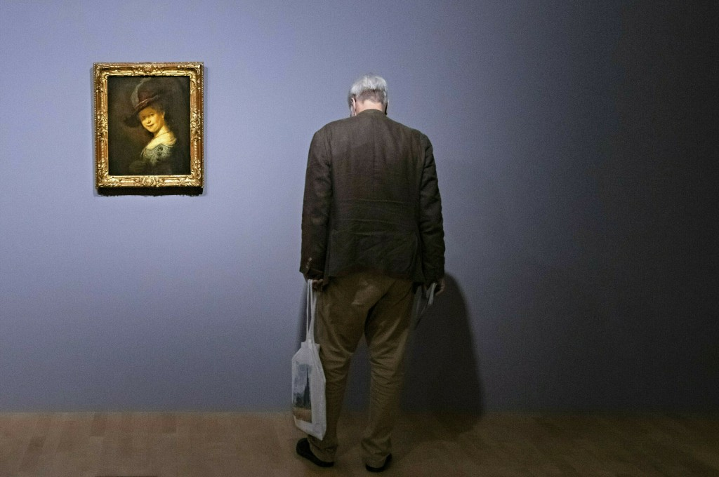 """A visitor stands near the painting """"Bust of a Young Woman Smiling (Saskia van Uylenburgh)"""" (1633) by Rembrandt van Rijn during a press preview of the ..."""