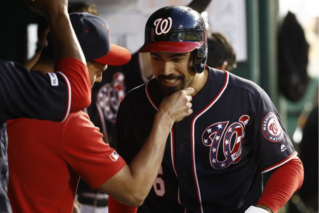 A member of the Washington Nationals tugs on Anthony Rendon's beard as Rendon celebrates his solo home run with teammates in the dugout during the six...