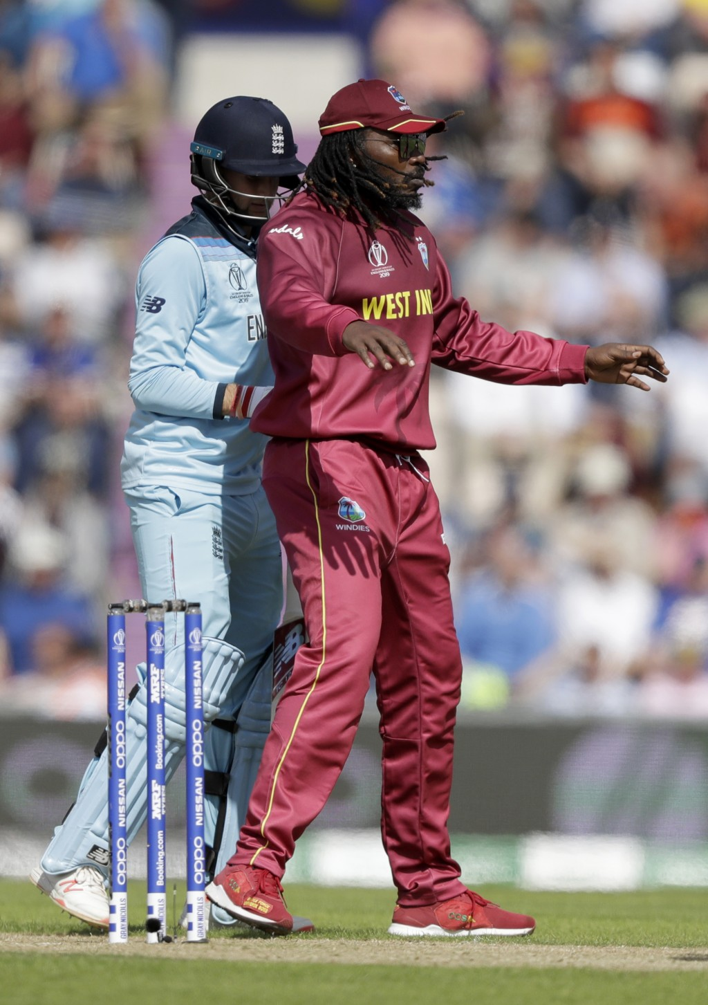 West Indies' Chris Gayle, right, jokingly blocks the way of England's Joe Root during one of his spin bowling overs during the Cricket World Cup match