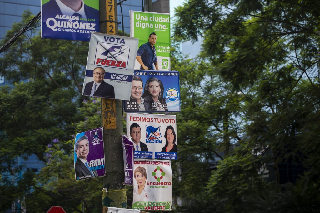 In this Thursday, June 13, 2019, photo, campaign posters hang on a pole on Reforma Avenue in Guatemala City. The road to Sunday's presidential electio