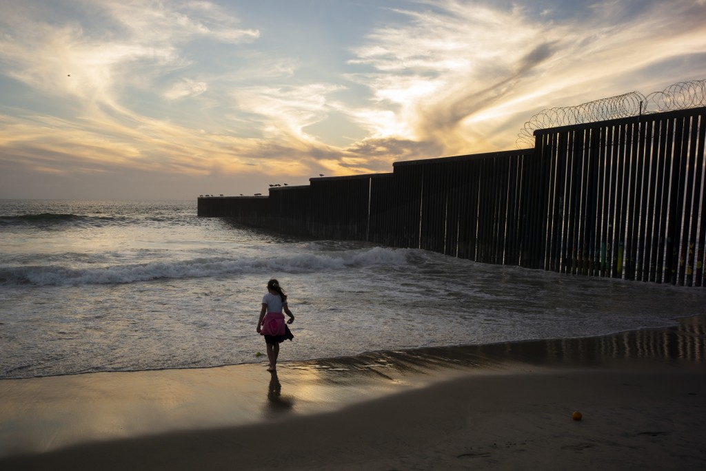 A girl plays along the border wall, right, separating San Diego from Tijuana, Mexico, where it meets the Pacific Ocean, Tuesday, June 11, 2019, in Tij...