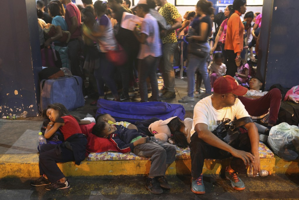 Venezuelan migrants rest while another group stands in line to enter am immigration office in Tumbes, Peru, Friday, June 14, 2019. Venezuelan citizens