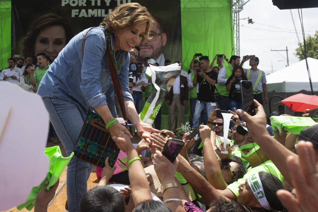 Sandra Torres, presidential candidate of the National Unity of Hope party, UNE, shakes hands with supporters during her closing campaign rally prior t
