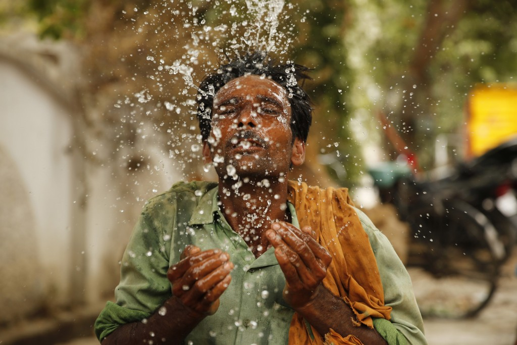 A worker splashes water on his face to cool himself on a hot summer afternoon in Prayagraj, Uttar Pradesh, India, Thursday, June 13, 2019. Severe heat...