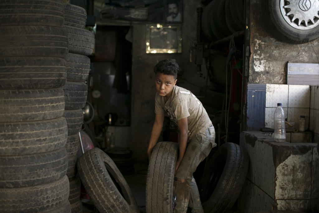 A boy carries a tire into a repair shop where he works in Cairo, Egypt, Wednesday, June 12, 2019. The United Nations has designated June 12 as World D...