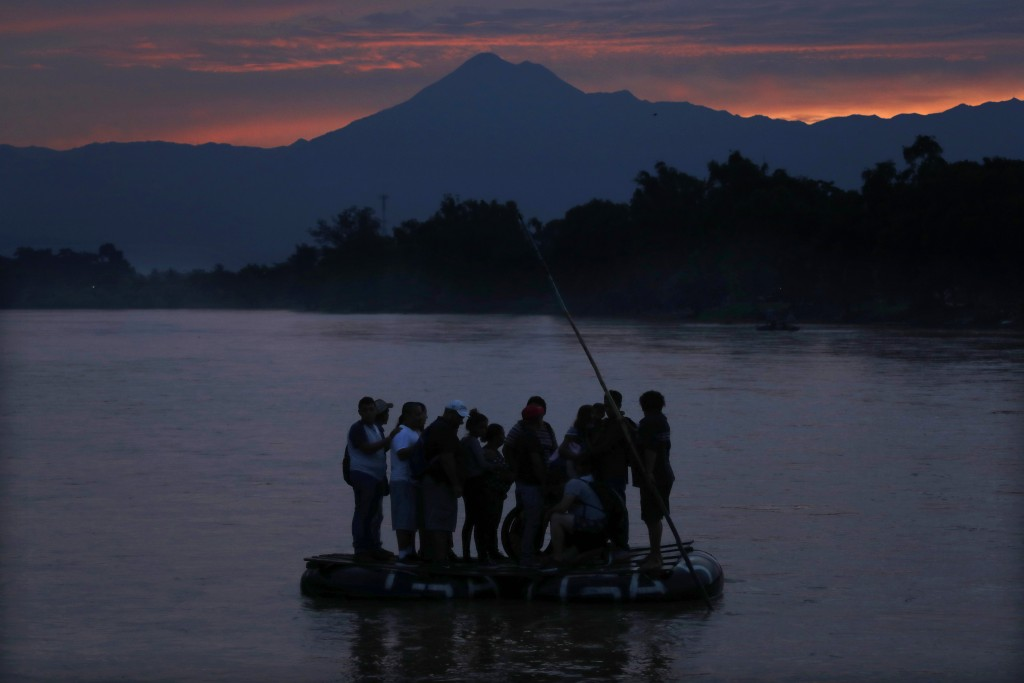 Central American migrants stand on a raft to cross the Suchiate River from Guatemala to Mexico, with the Tacana volcano in the background, near Ciudad...