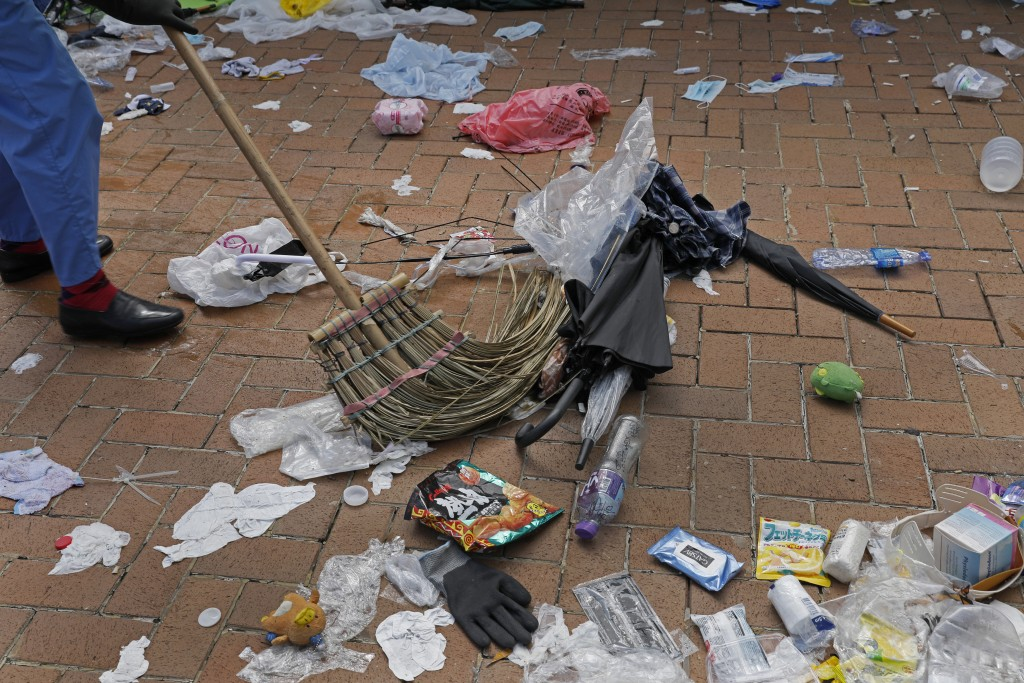 In this Friday, June 14, 2019, photo, a worker cleans up broken umbrellas left in the aftermath of Wednesday's violent protest against proposed amendm