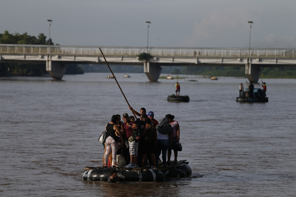 Migrants cross by raft from Tecun Uman, Guatemala, left, to Ciudad Hidalgo, Mexico, on Friday, June 14, 2019. Raftsmen and riverfront business operato