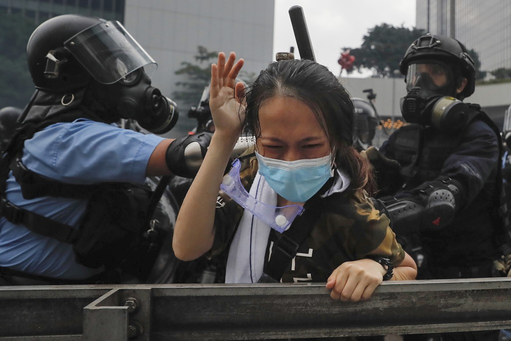 A protester is confronted by riot police during a massive demonstration outside the Legislative Council in Hong Kong on Wednesday, June 12, 2019. Tens