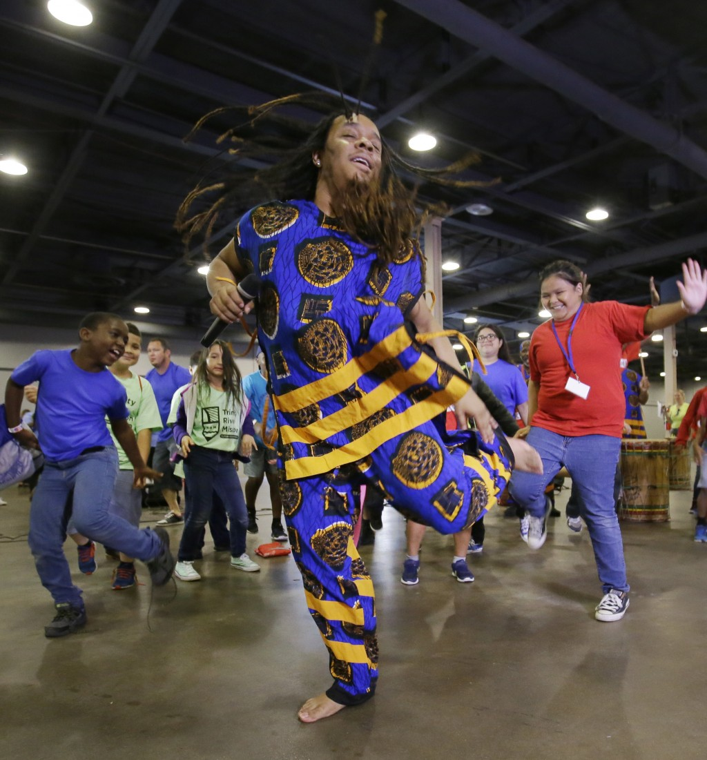 FILE - In this June 19, 2017, file photo, T.J. with the Bandan Koro African Dance Ensemble leads children dancing during a Juneteenth celebration at F...