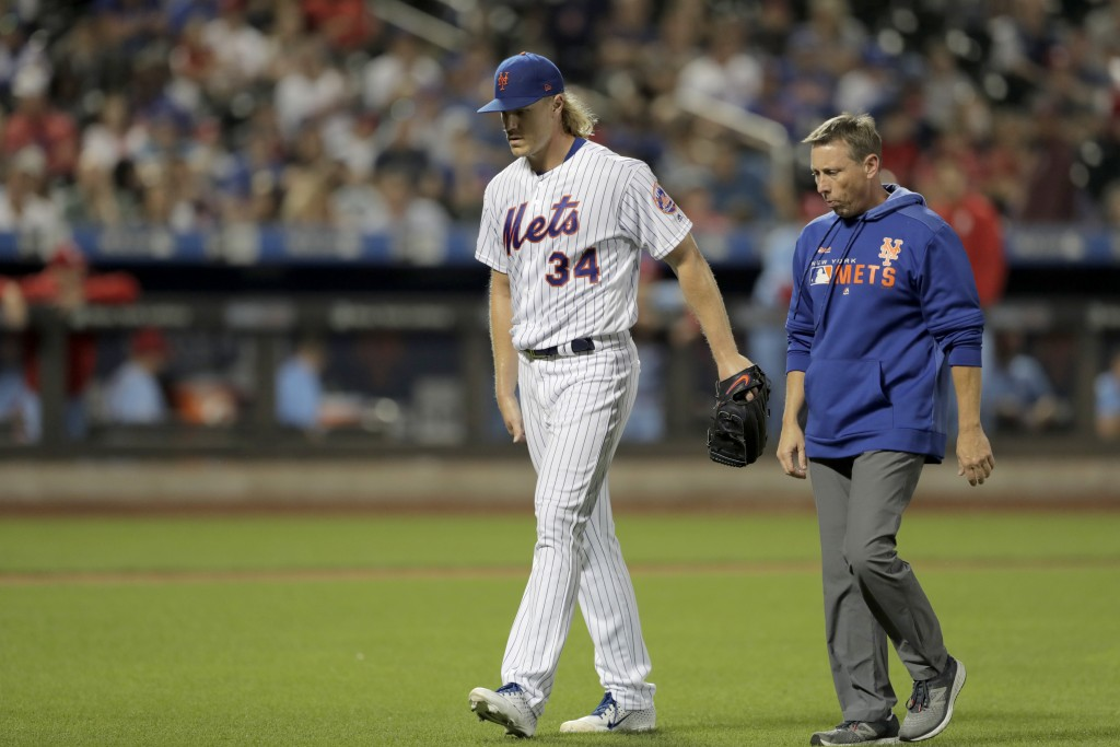 New York Mets starting pitcher Noah Syndergaard (34) touches his leg as he walks with a trainer while leaving the baseball game against the St. Louis ...