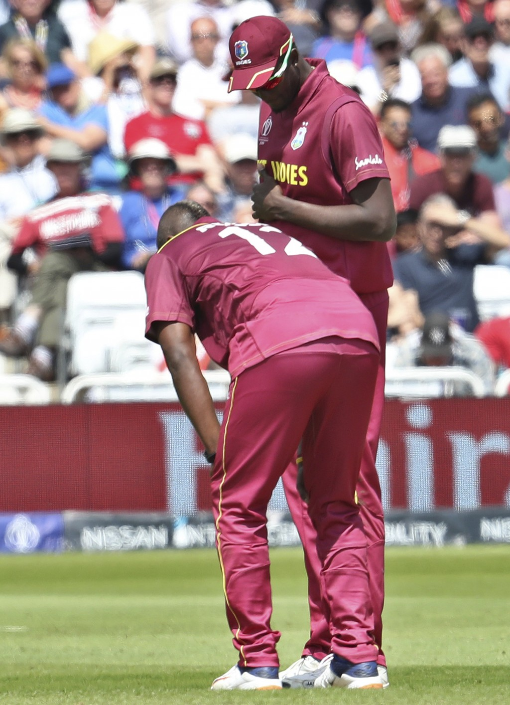 West Indies' captain Jason Holder, right, attend to teammate Andre Russell before he walked off the filed during the Cricket World Cup match between A...
