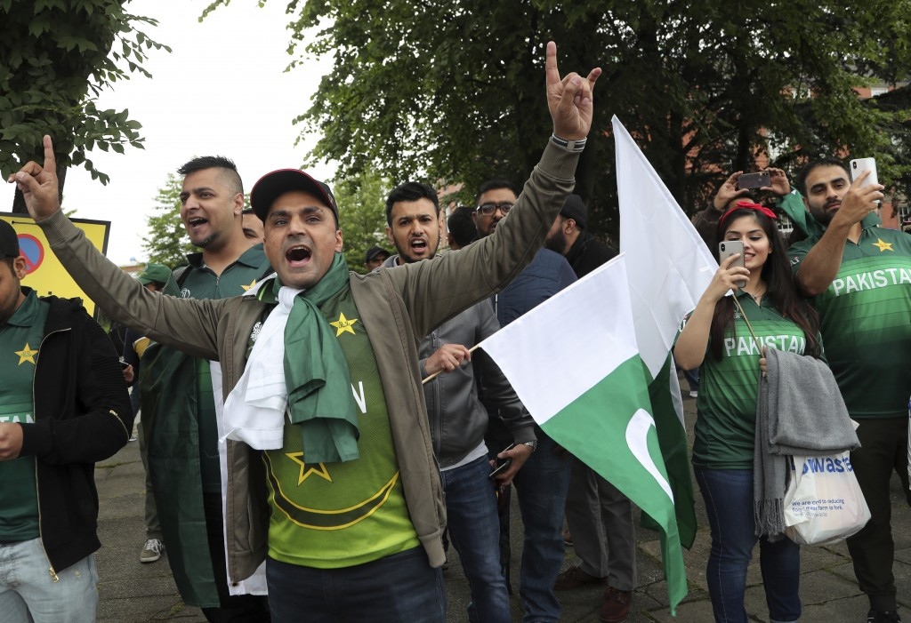 Pakistan fans dance as they arrive before the start of the Cricket World Cup match between India and Pakistan outside Old Trafford in Manchester, Engl