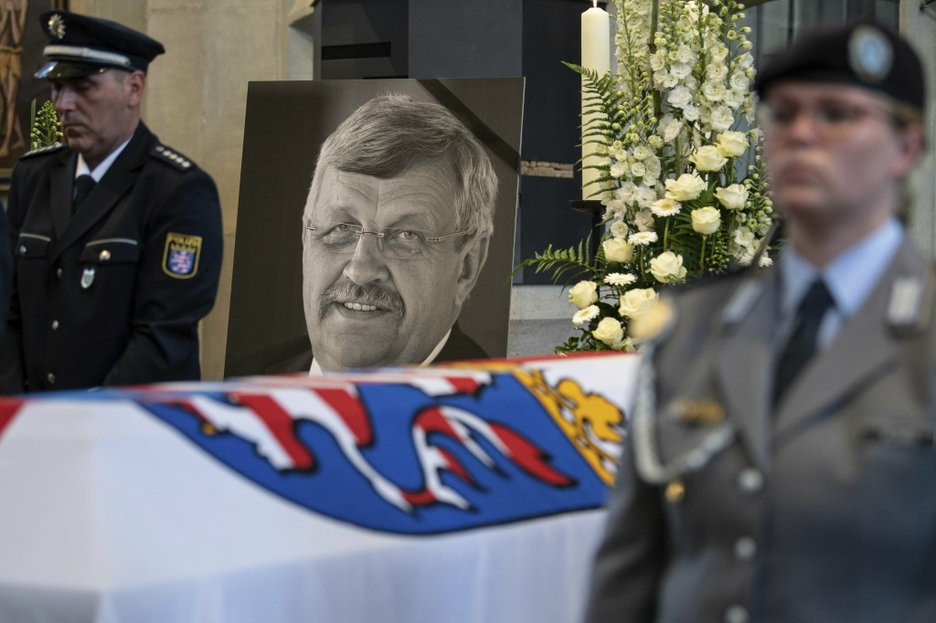FILE-In this June 13, 2019 file photo a picture of Walter Luebcke stands behind his coffin during the funeral service in Kassel, Germany. German autho...