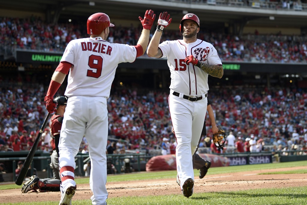 Washington Nationals' Matt Adams (15) celebrates his home run with Brian Dozier (9) during the first inning of a baseball game against the Arizona Dia