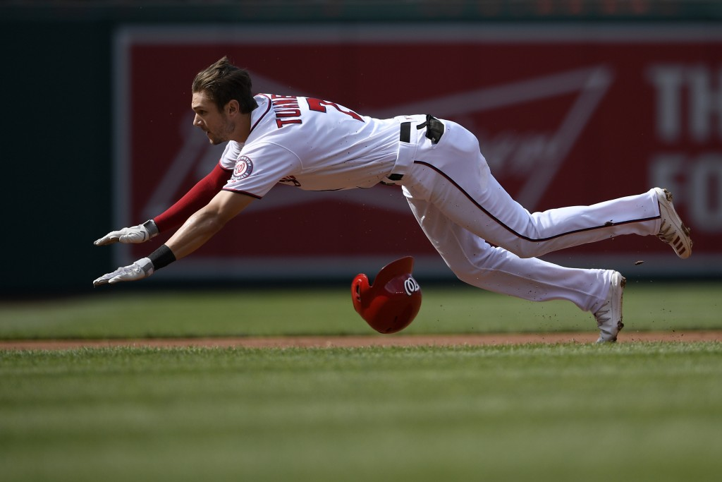 Washington Nationals' Trea Turner dives towards third for a triple during the first inning of a baseball game against the Arizona Diamondbacks, Saturd...