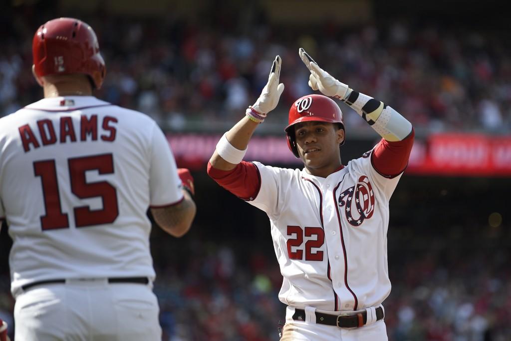 Washington Nationals' Juan Soto (22) celebrates his home run with Matt Adams (15) during the first inning of a baseball game against the Arizona Diamo