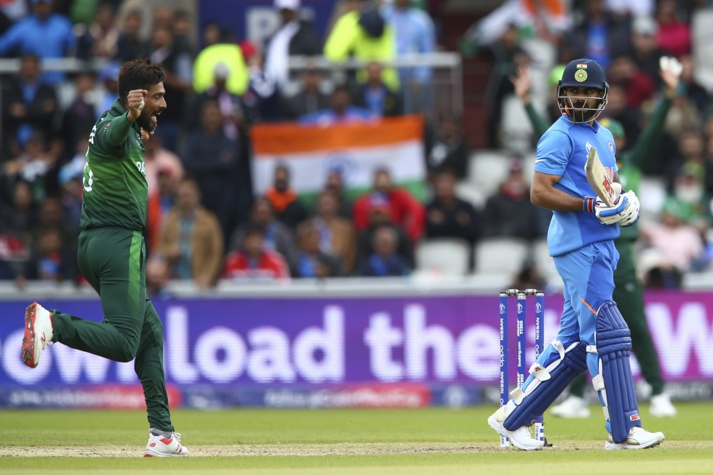 India's captain Virat Kohli, right, leaves the pitch after he is caught by Pakistan's captain Sarfaraz Ahmed off the bowling of Pakistan's Mohammad Am...