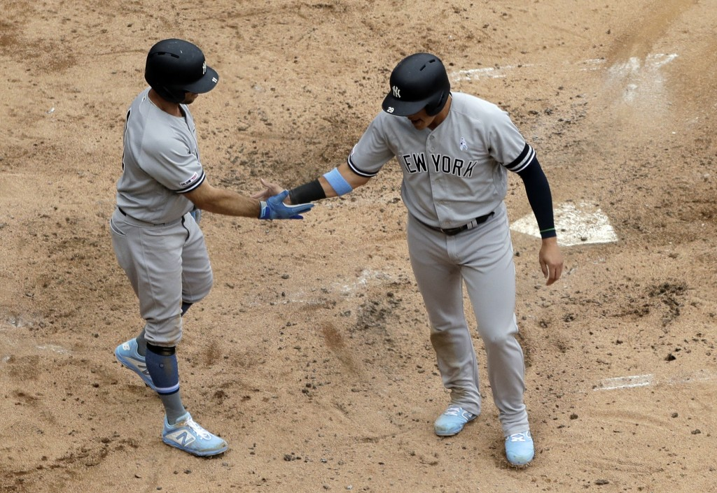 New York Yankees' Brett Gardner, left, celebrates with Gio Urshela after scoring on a two-run single by Austin Romine during the third inning of a bas