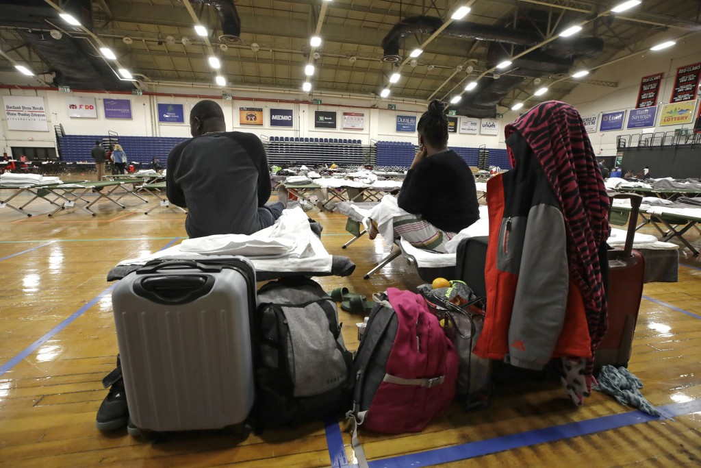 In this June 13, 2019 photo, a migrant couple sit with their belongings inside the Portland Exposition Building in Portland, Maine. Maine's largest ci...