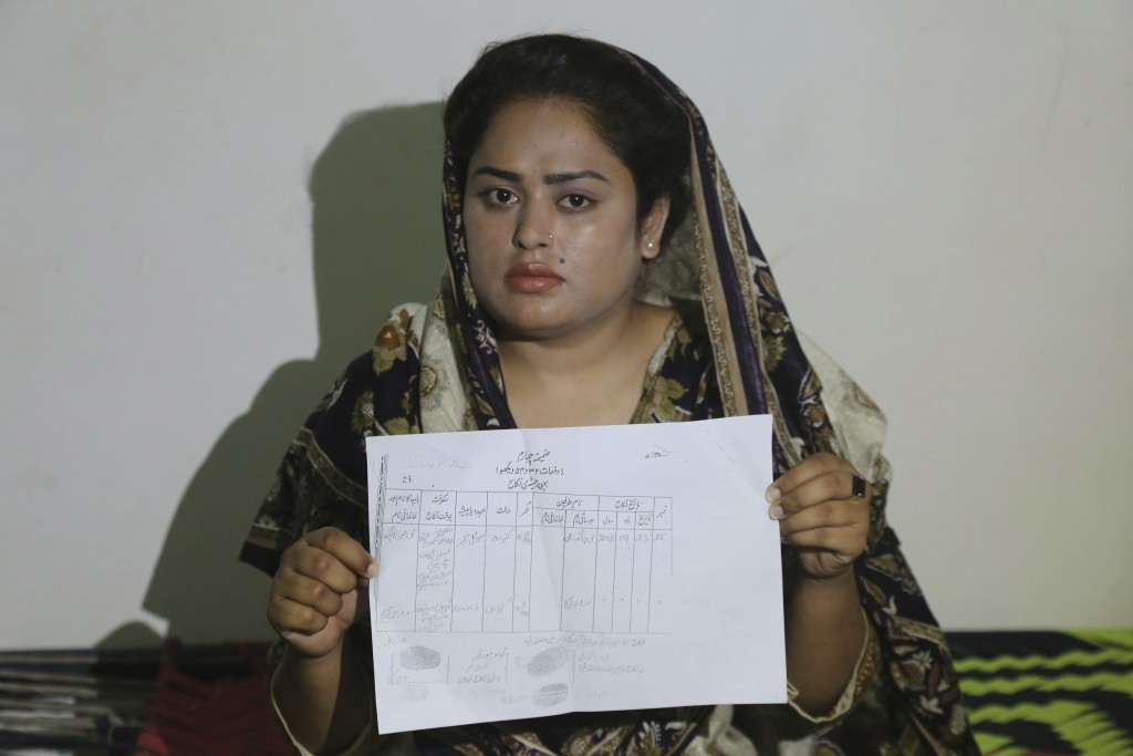 In this May 14, 2019, photo, Pakistani Christian Natasha Masih girl shows her marriage certificate during an interview in Faisalabad, Pakistan. Natash...