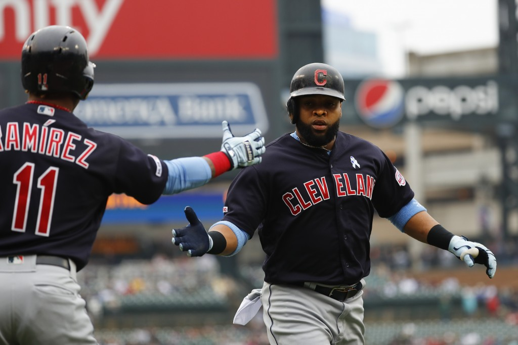 Cleveland Indians' Carlos Santana celebrates scoring with Jose Ramirez (11) against the Detroit Tigers in the first inning of a baseball game in Detro