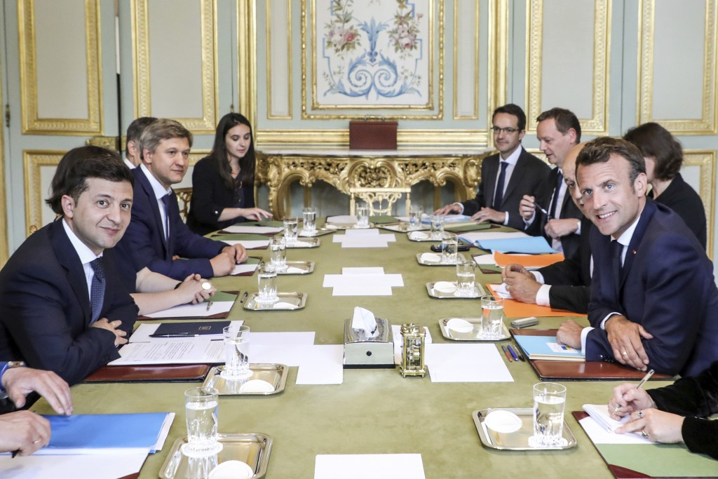 French President Emmanuel Macron, right, poses with Ukrainian President Volodymyr Zelenskiy, left, during a meeting at the Elysee Palace, in Paris, Mo...