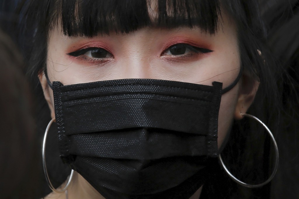 A protester with a mask gathers with others near the Legislative Council as they continuing protest against the unpopular extradition bill in Hong Kon