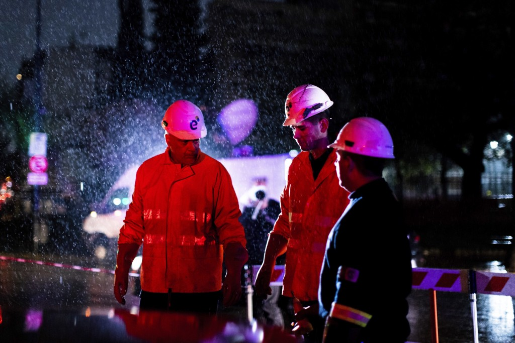 Technicians of Edenor electricity company stand under the rain as they work to fix a generator during a blackout in Buenos Aires, Argentina, Sunday, J...