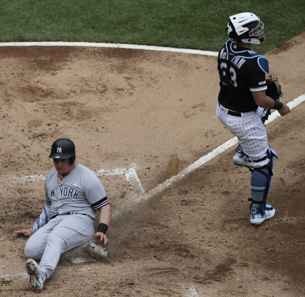New York Yankees' Luke Voit, left, scores on a two-run single by Brett Gardner as Chicago White Sox catcher James McCann looks to the field during the...
