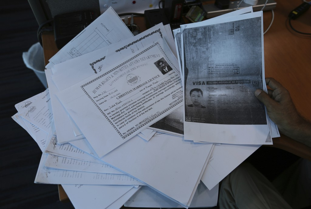 In this photo taken on May 27, 2019, a person shows photocopies of dozens of marriage contracts and other documents collected by a Pakistani security