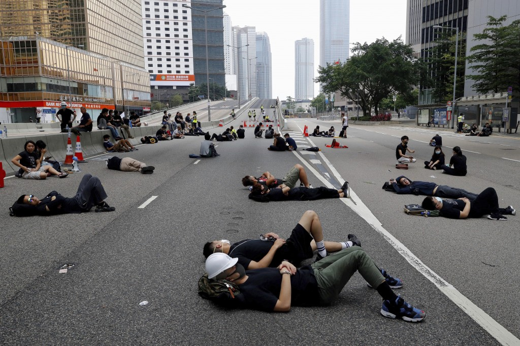 Protesters who camped out overnight take a rest along a main road near the Legislative Council after continuing protest against the unpopular extradit