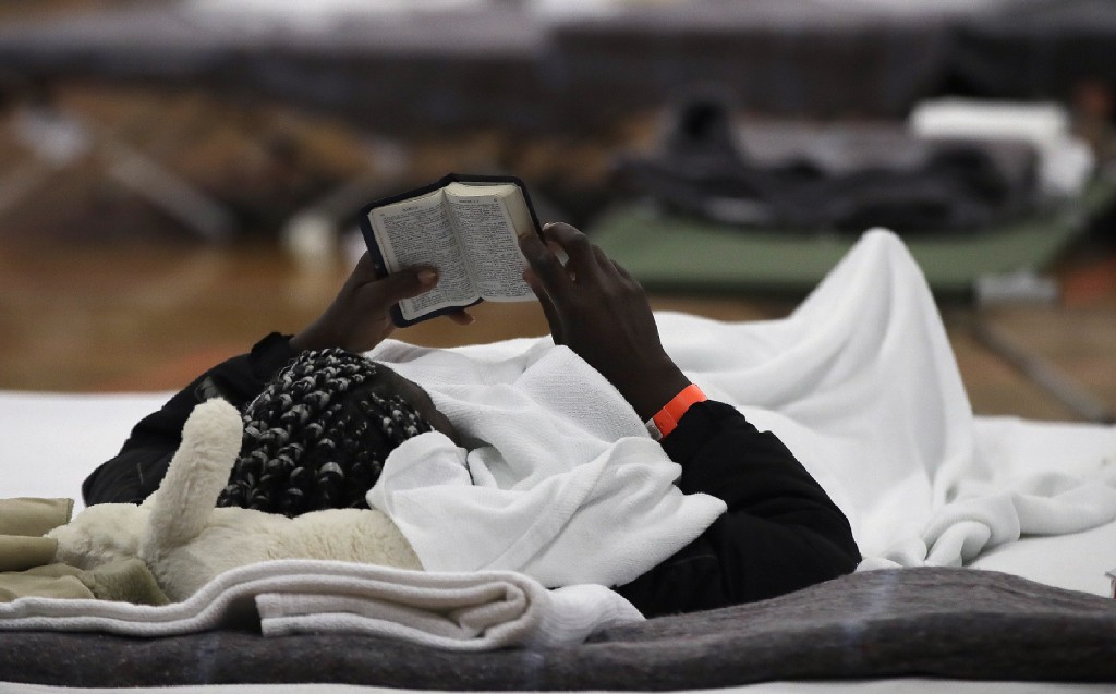 In this June 13, 2019 photo, a migrant woman reads a Bible as she rests inside the Portland Exposition Building in Portland, Maine. Maine's largest ci