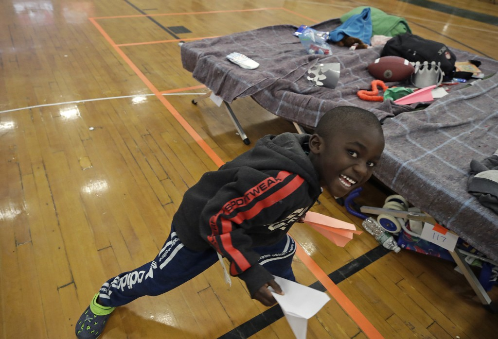 In this June 13, 2019 photo, a migrant boy plays inside the Portland Exposition Building in Portland, Maine. Maine's largest city has repurposed the b...