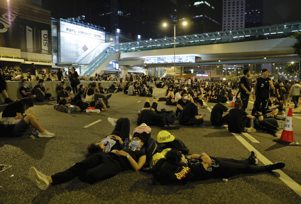Protesters rest on the streets as they continue a protest overnight near the Legislative Council into the early hours of Monday, June 17, 2019 in Hong
