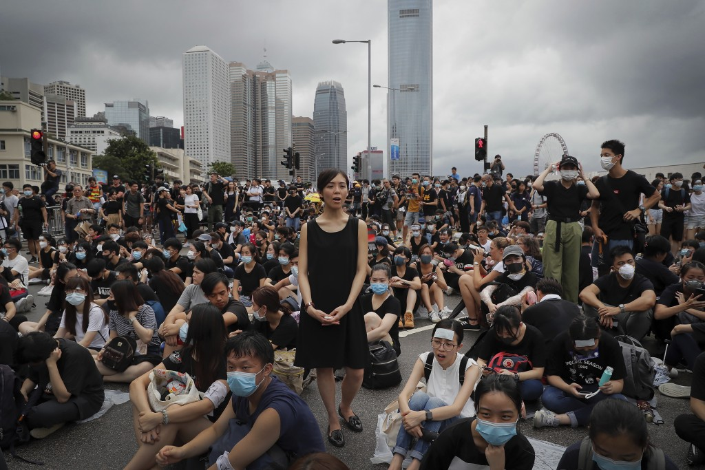 A protester, center, calls Hong Kong Chief Executive Carrie Lam to step down as she and others continue protest against the unpopular extradition bill