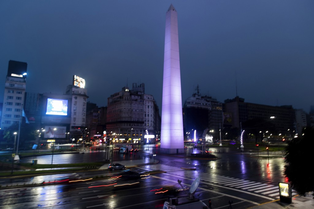 Cars drive on the 9 de Julio Ave, past the illuminated Obelisk monument in Buenos Aires, Argentina, early Monday morning, June 17, 2019. As lights tur