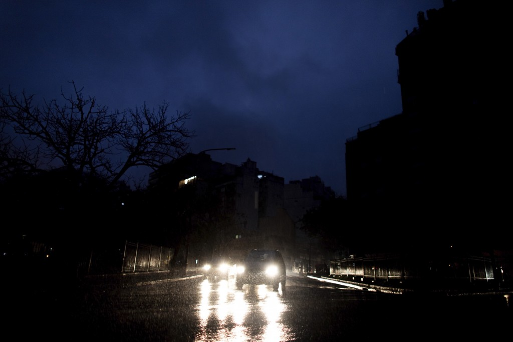 Cars drive through an unlit street during a blackout in Buenos Aires, Argentina, Sunday, June. 16, 2019. A massive blackout left tens of millions of p...