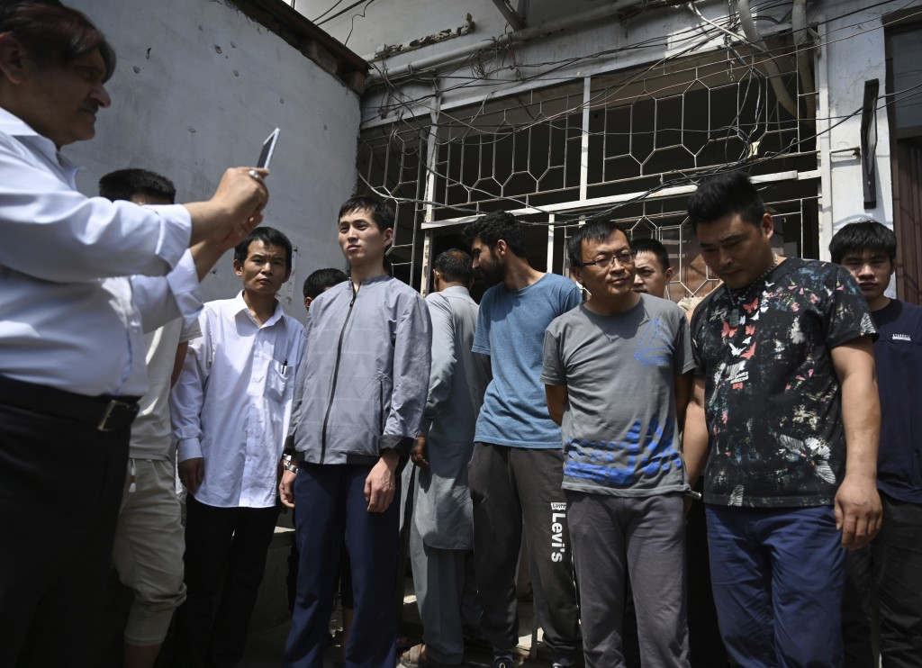 FILE - In this May 9, 2019, file photo, a Pakistani official takes pictures of detained Chinese nationals on alleged involvement in a trafficking gang...