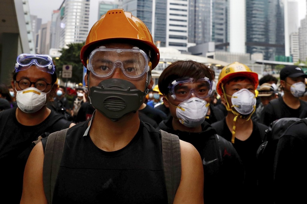 Protesters wearing protection gears march toward the Legislative Council as they continue to protest against the extradition bill in Hong Kong, Monday...