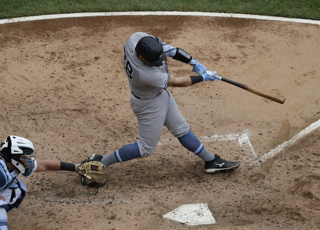 New York Yankees' Austin Romine hits a two-run single against the Chicago White Sox during the third inning of a baseball game in Chicago, Sunday, Jun