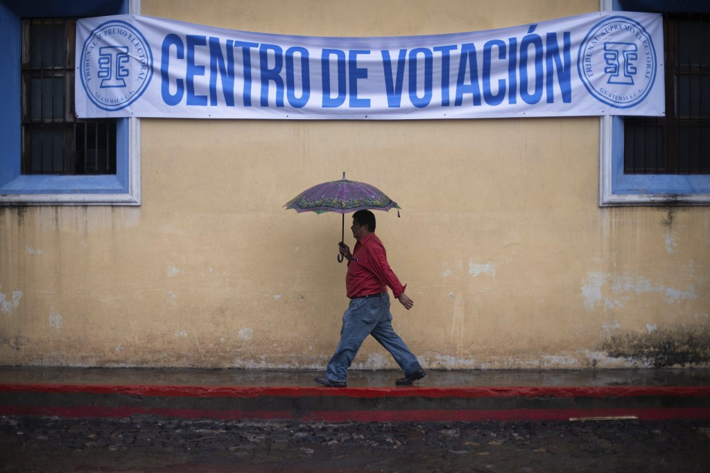 FILE - In this June 16, 2019 file photo, a man walks in the rain to a polling station during general elections in Antigua, Guatemala. Supreme Electora...
