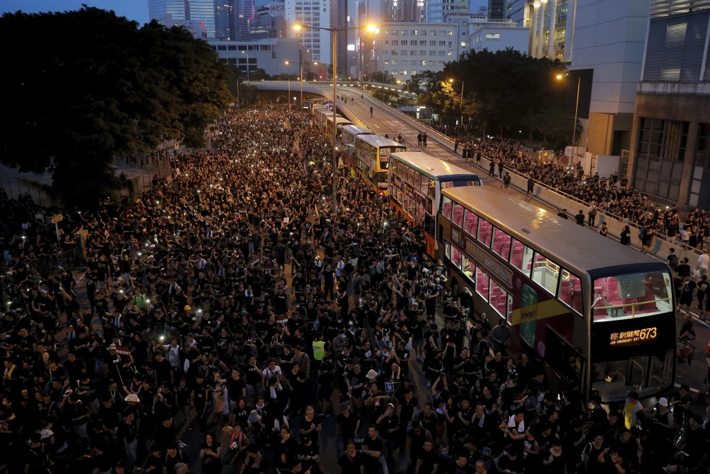 In this Sunday, June 16, 2019, photo, protesters gather on a main road near the Legislative Council as they continuing protest against the unpopular e