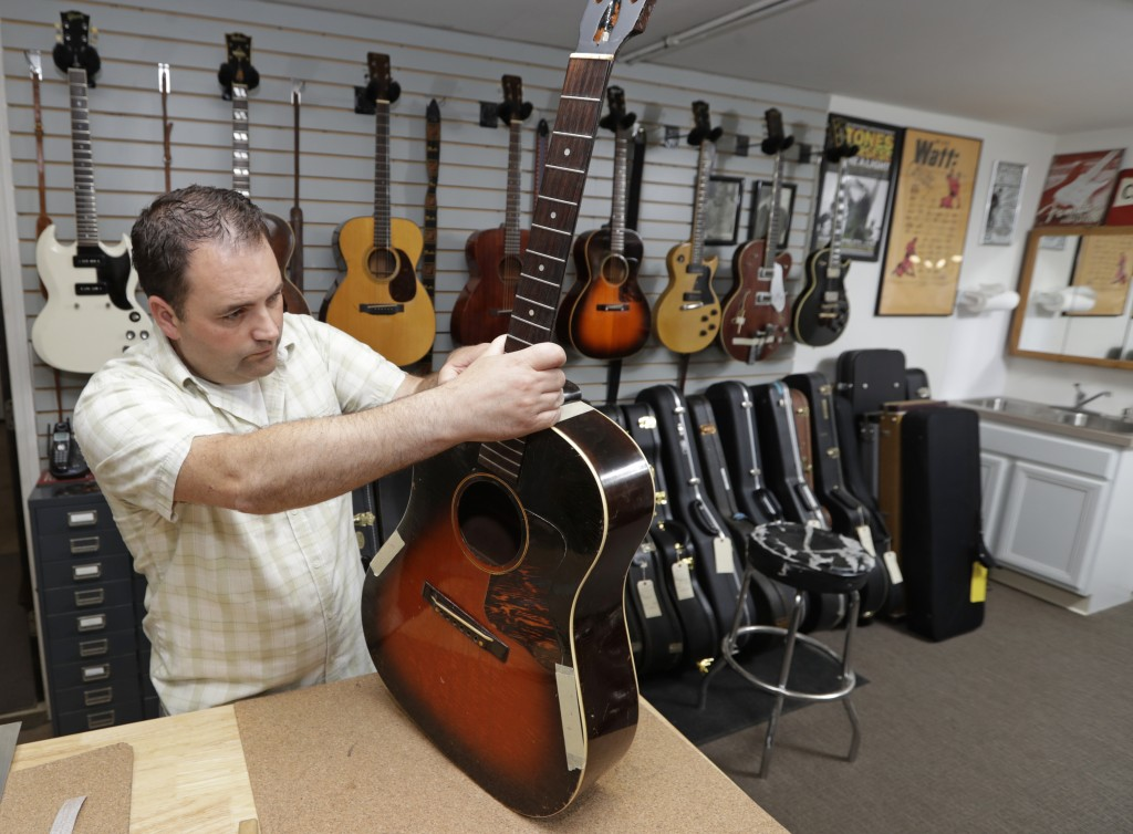 Jacob Tuel, owner of Burning River Guitars, repairs the neck of a guitar, Monday, June 10, 2019, in Akron, Ohio. Tuel named his guitar shop after the