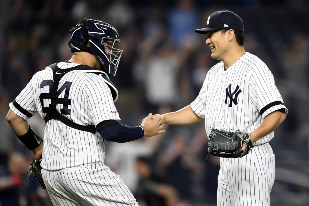 New York Yankees starter Masahiro Tanaka, right, greets catcher Gary Sanchez (24) after pitching a complete baseball game shutout against the Tampa Ba...