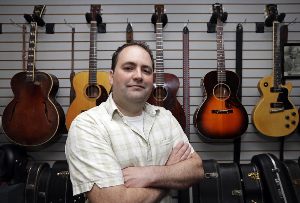 Jacob Tuel, owner of Burning River Guitars, poses for a photo in his workshop, Monday, June 10, 2019, in Akron, Ohio. Tuel named his guitar shop after