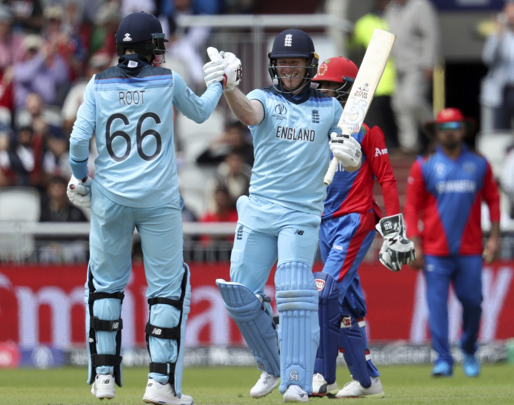 England's captain Eoin Morgan, right, celebrates with teammate Joe Root after scoring a century during the Cricket World Cup match between England and...